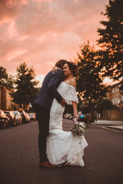 Pink Sunset Portrait with Bride in Off The Shoulder Grace Loves Lace Dress and Groom in Blue Blazer