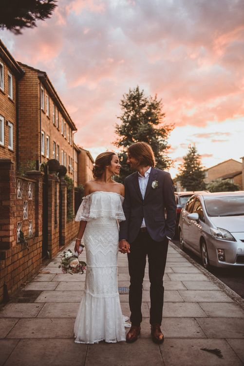 Bride in Off The Shoulder Grace Loves Lace Wedding Dress and Groom in Blue Blazer  Walking During Pink Sunset