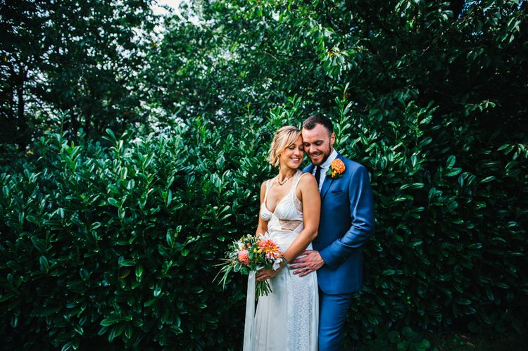 Bride in Racerback Alexander Wang Wedding Dress | Groom in Blue Ted Baker Suit | Bright Bouquet of Dahlias with Trailing Ribbon | Colourful Pennard House Wedding With Bride Wearing Racerback Dress | Allison Dewey Photography