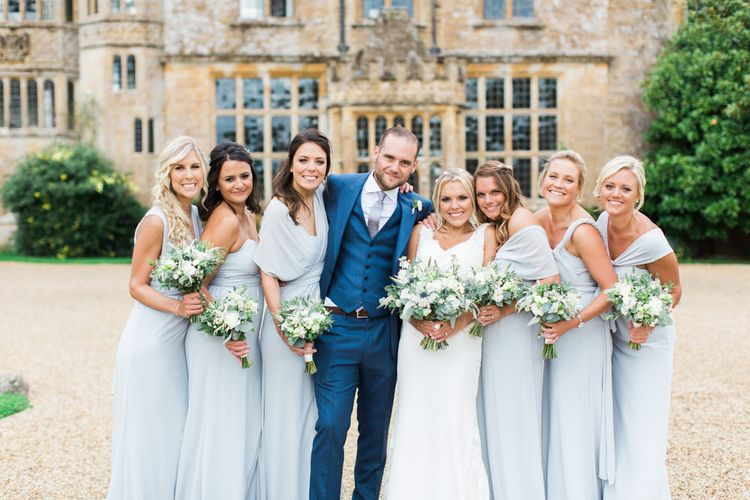 Bride and Groom with Bridesmaids in Front of The Wedding Venue