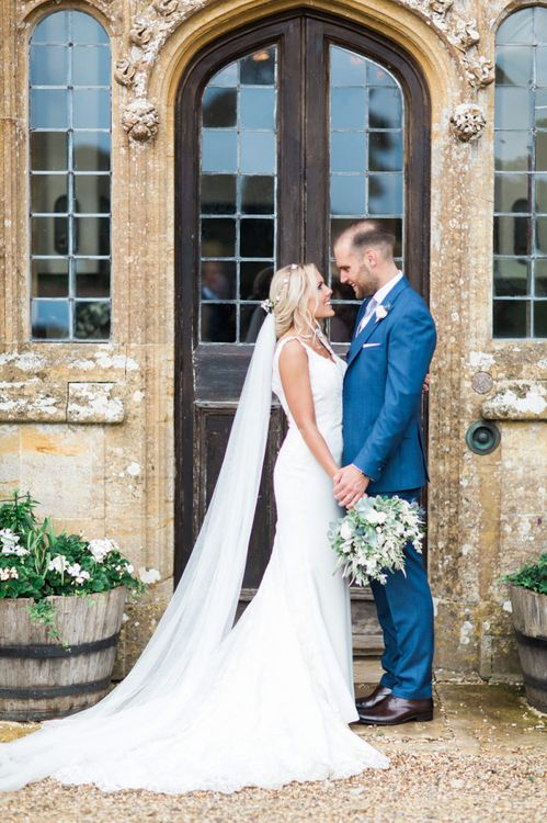 Bride in St Patrick La Sposa Wedding Dress and Groom in Blue Reiss Suit Holding Hands