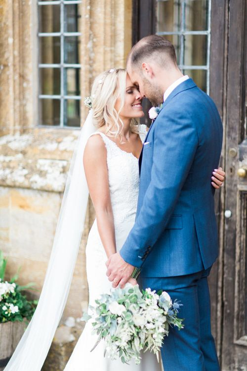 Bride in St Patrick La Sposa Wedding Dress and Groom in Blue Reiss Suit Embracing