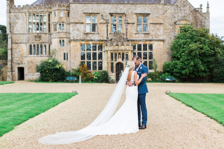 Bride in St Patrick La Sposa Wedding Dress and Groom in Blue Reiss Suit in Front of Their Wedding Venue