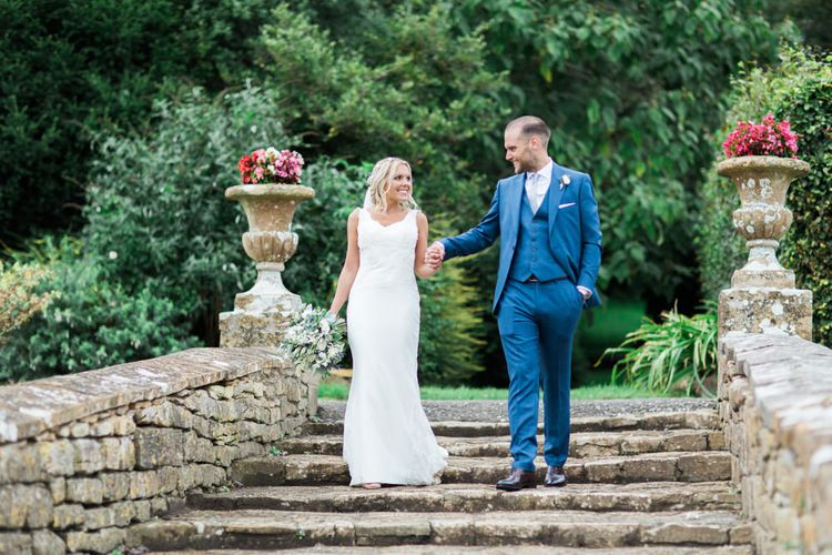 Bride in St Patrick La Sposa Wedding Dress and Groom in Blue Reiss Suit Walking Down Steps