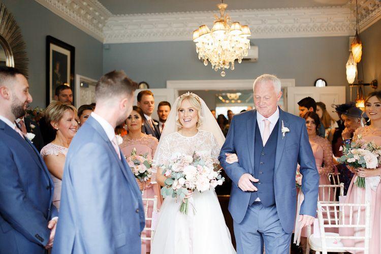 Bride walks down the aisle to meet her groom