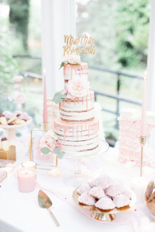 Pink drip wedding cake on dessert table