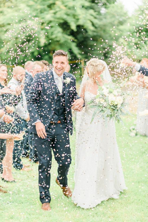 Confetti Moment with Bride in Romantic Wedding Dress and Groom in Navy Moss Bros. Suit