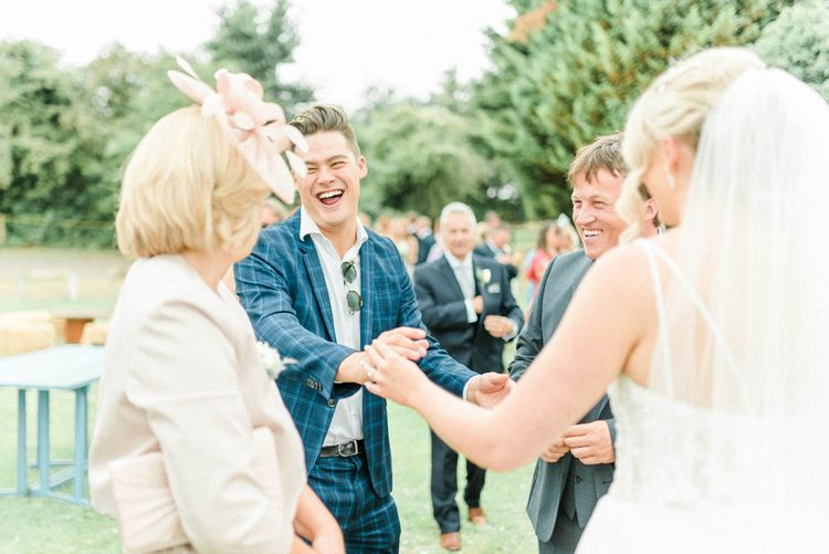 Wedding Guest in Blue Checked Suit Laughing with Bride