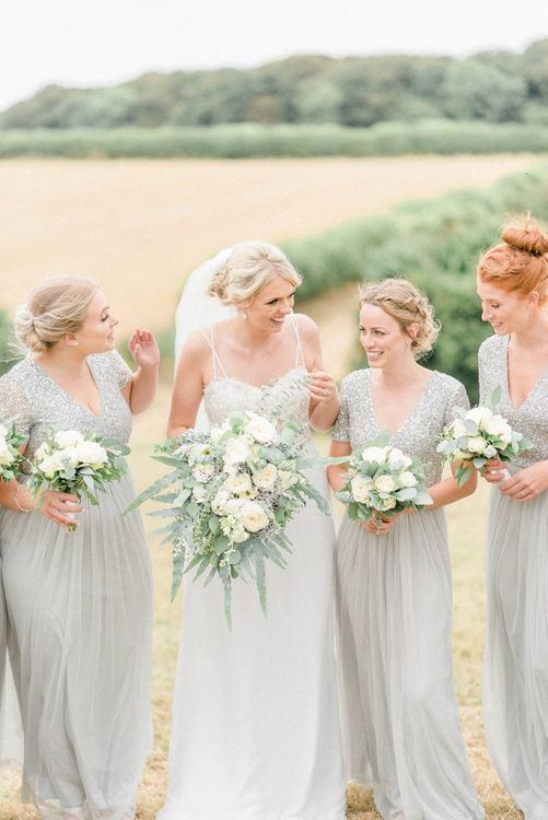 Bride in Lace Bodice Wedding Dress with Floaty Skirt and Straps Laughing with Bridesmaid in Lace & Sequin MAYA Dresses