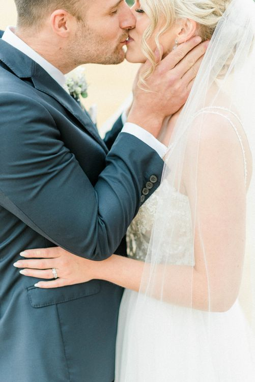 Groom in Moss Bros. Navy Suit Kissing his Bride in Lace Wedding Dress and Cathedral Veil