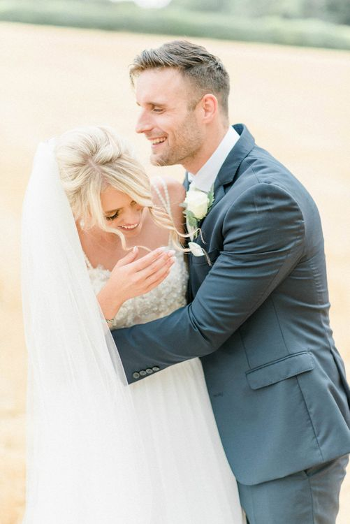 Bride in Lace Wedding Dress and Cathedral Veil laughing with Her Groom in  Navy Moss Bros. Suit