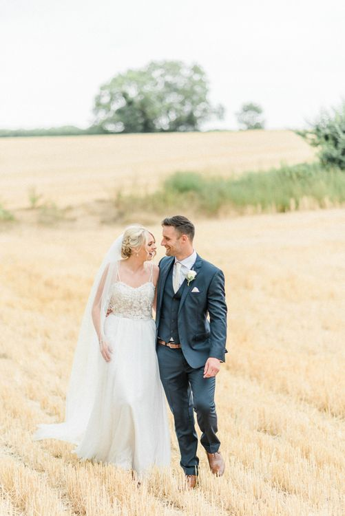 Bride in Lace Wedding Dress and Cathedral Veil and Groom in  Navy Moss Bros. Suit Walking Through a Corn Field