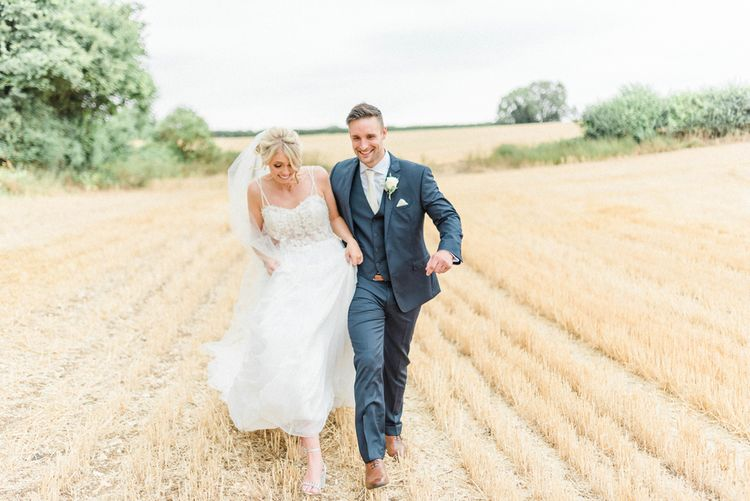 Bride in Lace Wedding Dress and Cathedral Veil and Groom in  Navy Moss Bros. Suit Holding Hands in a Corn Field