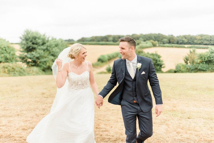 Bride in Lace Wedding Dress and Cathedral Veil and Groom in  Navy Moss Bros. Suit Laughing Together
