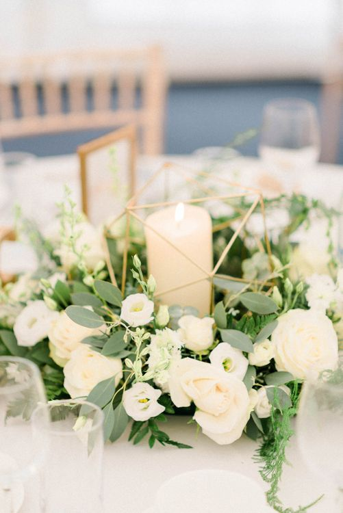 Table Centrepiece with White and Green Flowers, Church Candles and Gold Geometric Decor