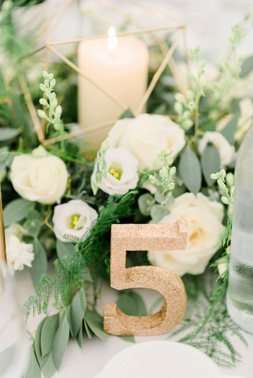 Table Centrepiece with White and Green Flowers, Church Candle and Gold Glitter Table Number for Wedding