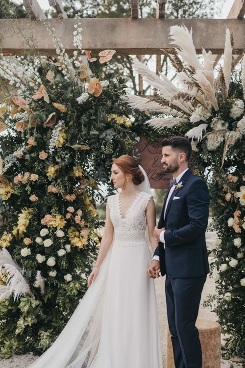 Bride in Pronovias Wedding Dress and Groom in Navy Suit Holding Hands in Front of a Peach Floral Arch