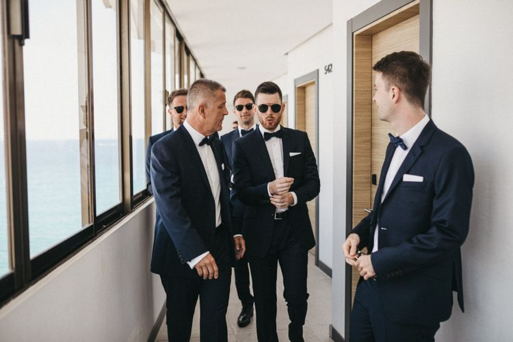 Stylish Groomsmen in Navy Suits with Bow Ties and Sunglasses