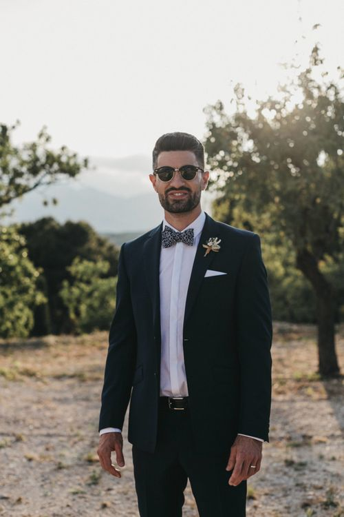 Stylish Groom in Navy Suit with Floral Bow Tie and Sunglasses