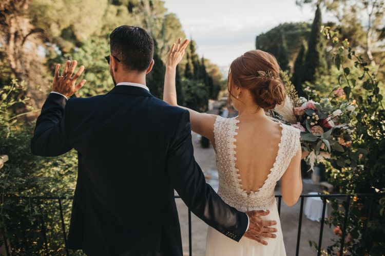 Bride in Backless Pronovias Wedding Dress and Groom in Navy Suit Waving to Their Wedding Guests on the Balcony