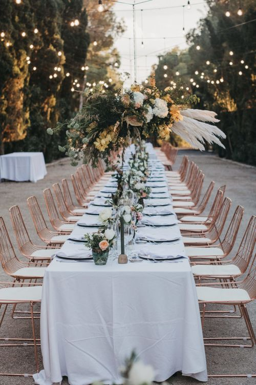 Long Wedding Reception Table with Peach Flowers, Pampas Grass Installation and Festoon Lights