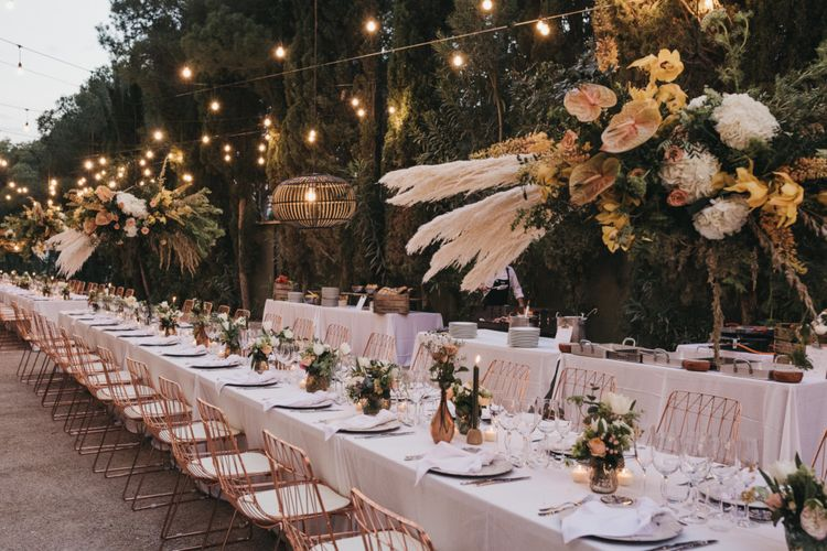 Outdoor Wedding Reception Decor with Festoon lights, Hanging Installation, Copper Vases and Chairs