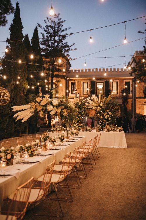 Outdoor Spanish Wedding Reception with Festoon Lights and Flower Installation
