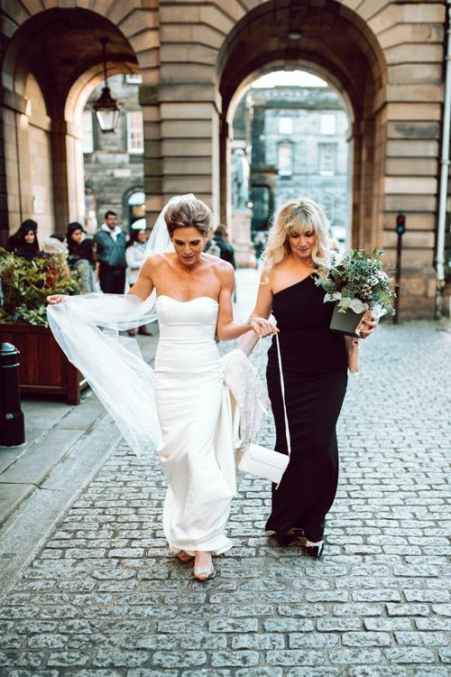 Bride and bridesmaid in black dress entering the Edinburgh City Chambers wedding ceremony