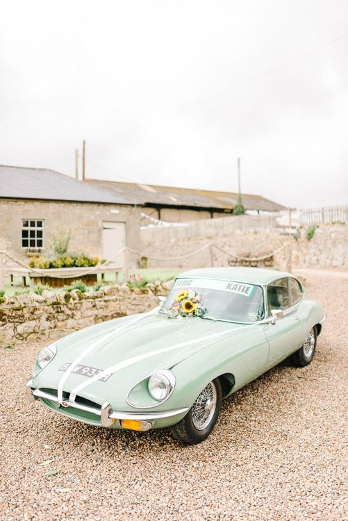 Vintage Wedding Car Decorated with Sunflowers and White Ribbon | Colourful Paper Cranes & Sunflower Wedding Décor in Rustic Barn | Sarah-Jane Ethan Photography