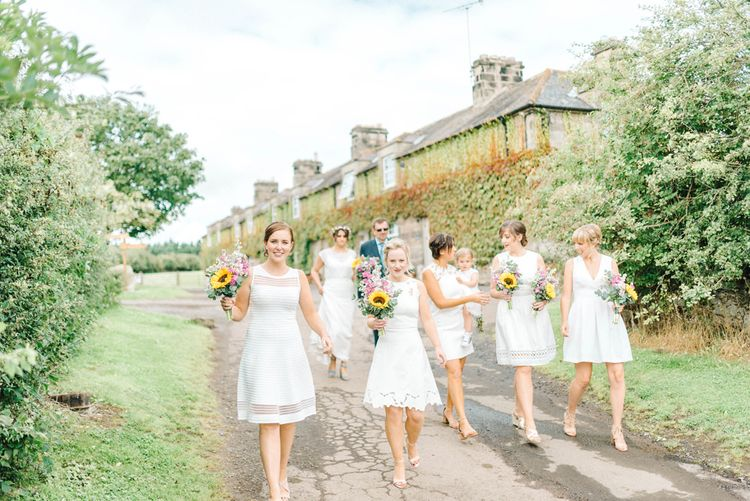 Bridesmaids in Mismatched Knee-Length White Dresses | Bright Bouquets with Sunflowers | Bride in Chiffon Polka Dot Dress by Kate Halfpenny | Bride Wearing Flower Crown | Bridal Plaited Up Do | Colourful Paper Cranes & Sunflower Wedding Décor in Rustic Barn | Sarah-Jane Ethan Photography