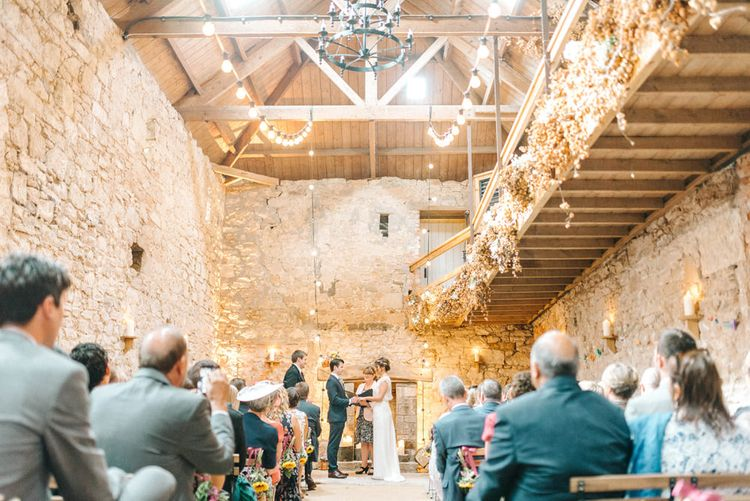 Bride in Chiffon Polka Dot Dress by Kate Halfpenny | Bridal Flower Crown | Groom in Blue Hugo Boss Suit with Dusty Blue Tie | Wedding Ceremony at Duxford Barns | Festoon Lights | Sunflower Chair Ends | Colourful Paper Cranes & Sunflower Wedding Décor in Rustic Barn | Sarah-Jane Ethan Photography