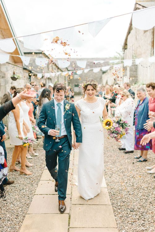 Bride in Chiffon Polka Dot Dress by Kate Halfpenny | Bridal Flower Crown | Groom in Blue Hugo Boss Suit with Dusty Blue Tie | Bright Bouquet with Sunflowers | Real Petal Confetti | White Bunting | Colourful Paper Cranes & Sunflower Wedding Décor in Rustic Barn | Sarah-Jane Ethan Photography
