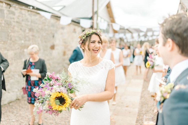 Bride in Chiffon Polka Dot Dress by Kate Halfpenny | Bridal Flower Crown | Bright Bouquet with Sunflowers | White Bunting | Colourful Paper Cranes & Sunflower Wedding Décor in Rustic Barn | Sarah-Jane Ethan Photography