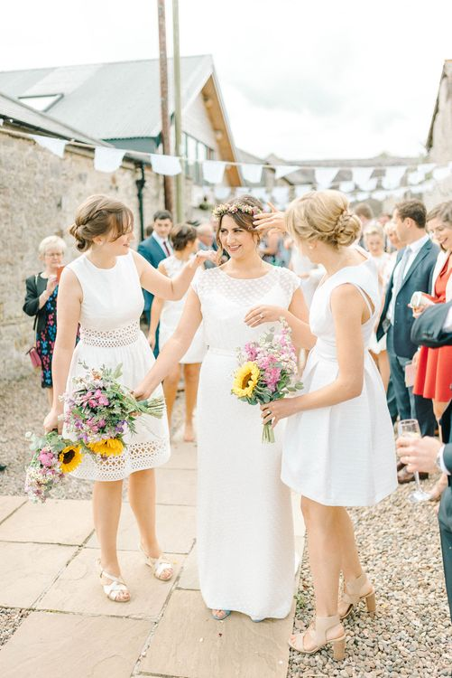 Bride in Chiffon Polka Dot Dress by Kate Halfpenny | Bridal Flower Crown | Bridesmaids in Mismatched Knee-Length White Dresses | Bright Bouquets with Sunflowers | Bridal Plaited Up Do | White Bunting | Colourful Paper Cranes & Sunflower Wedding Décor in Rustic Barn | Sarah-Jane Ethan Photography