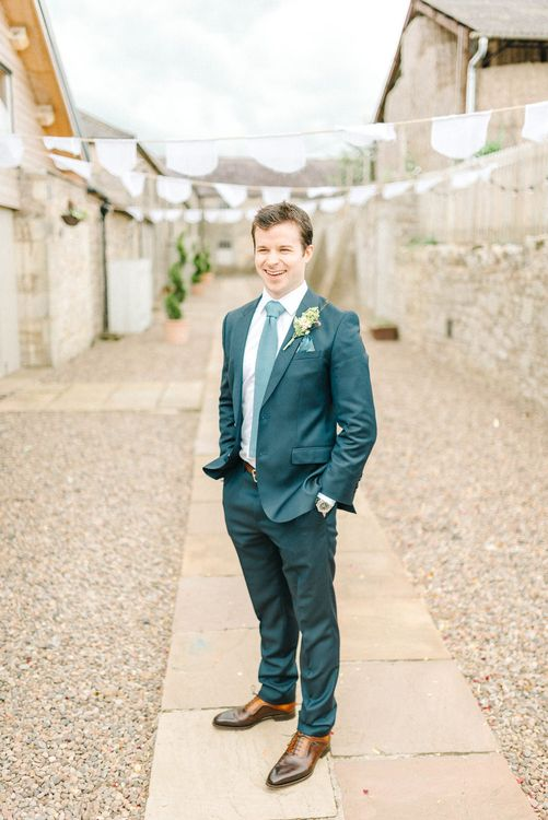 Groom in Blue Hugo Boss Suit with Dusty Blue Tie | White Bunting | Colourful Paper Cranes & Sunflower Wedding Décor in Rustic Barn | Sarah-Jane Ethan Photography
