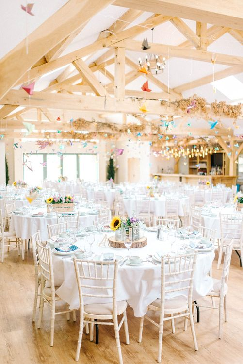 Paper Cranes Hanging from Barn Beams | Sunflower Table Centrepieces | Log Slice | Colourful Paper Cranes & Sunflower Wedding Décor in Rustic Barn | Sarah-Jane Ethan Photography