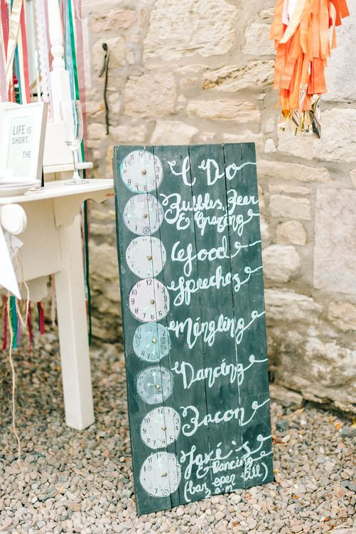 Rustic Order of the Day Chalkboard and Clocks Sign | Colourful Paper Cranes & Sunflower Wedding Décor in Rustic Barn | Sarah-Jane Ethan Photography
