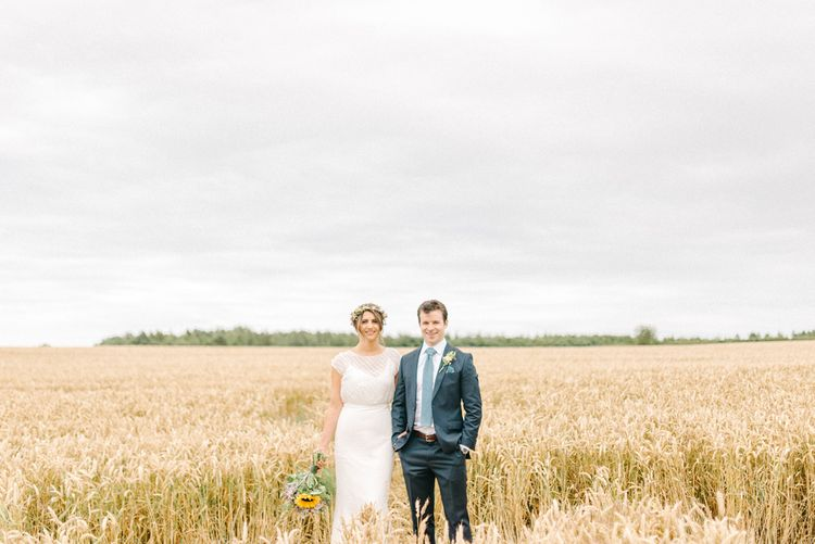 Bride in Chiffon Polka Dot Dress by Kate Halfpenny | Bridal Flower Crown | Groom in Blue Hugo Boss Suit with Dusty Blue Tie | Bright Bouquet with Sunflowers | Bridal Plaited Up Do | Colourful Paper Cranes & Sunflower Wedding Décor in Rustic Barn | Sarah-Jane Ethan Photography