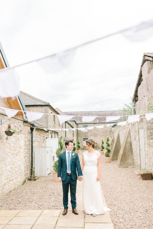 Bride in Chiffon Polka Dot Dress by Kate Halfpenny | Bridal Flower Crown | Groom in Blue Hugo Boss Suit with Dusty Blue Tie | Bright Bouquet with Sunflowers | Bridal Plaited Up Do | White Bunting | Colourful Paper Cranes & Sunflower Wedding Décor in Rustic Barn | Sarah-Jane Ethan Photography