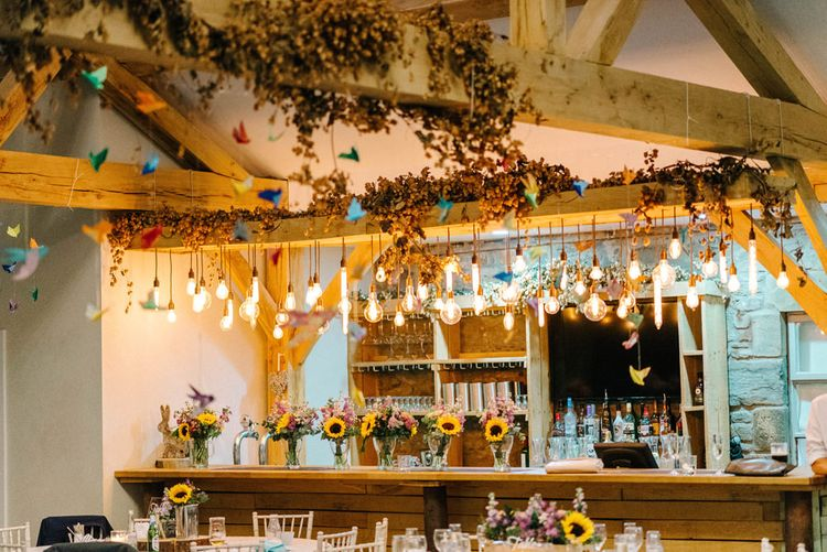Eddison Light Hanging Bar Decoration | Paper Cranes Hanging from Barn Beams | Sunflower Bouquets in Vases | Colourful Paper Cranes & Sunflower Wedding Décor in Rustic Barn | Sarah-Jane Ethan Photography