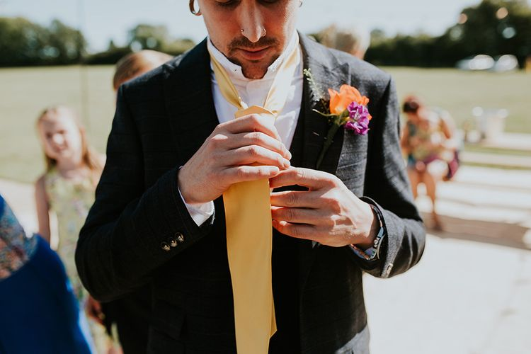 Groom wears yellow tie to match the canary yellow bridesmaid dresses