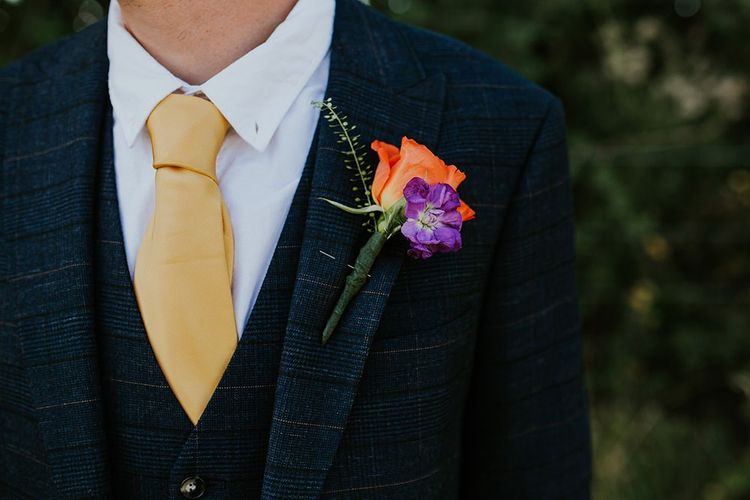 Groom wears yellow tie to match the canary yellow bridesmaid dresses with bright floral buttonhole