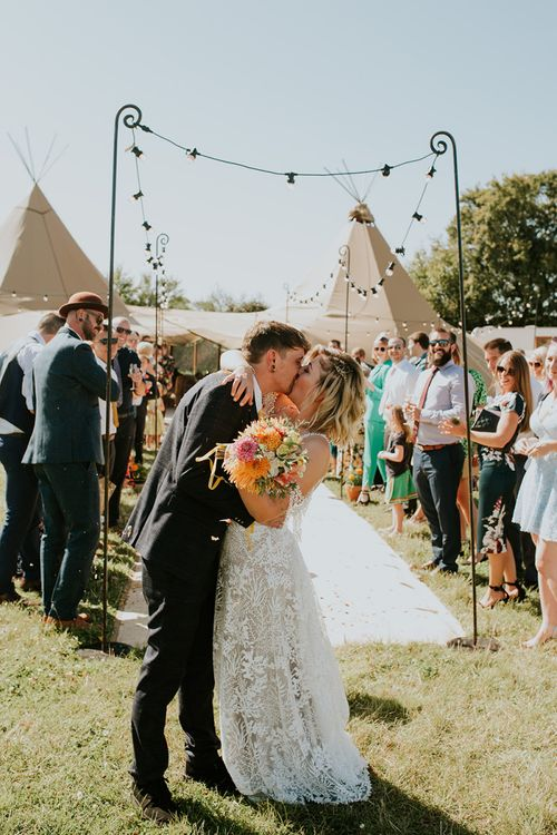 Bride and groom kiss after ceremony in PapaKata tipi