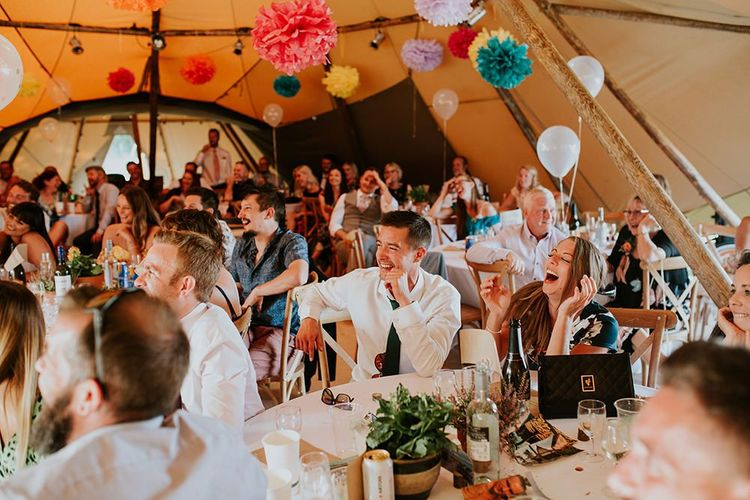 Guests enjoy wedding speeches with bright pompom decor