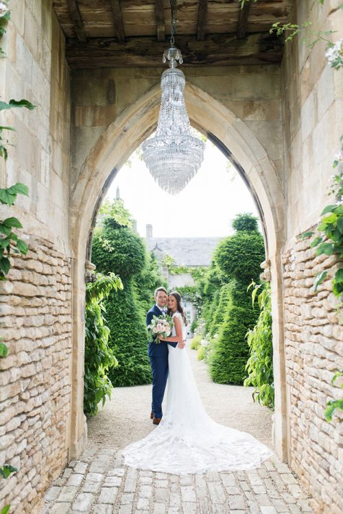 Bride and Groom Portrait Under The Crystal Chandelier at The Lost Orangery
