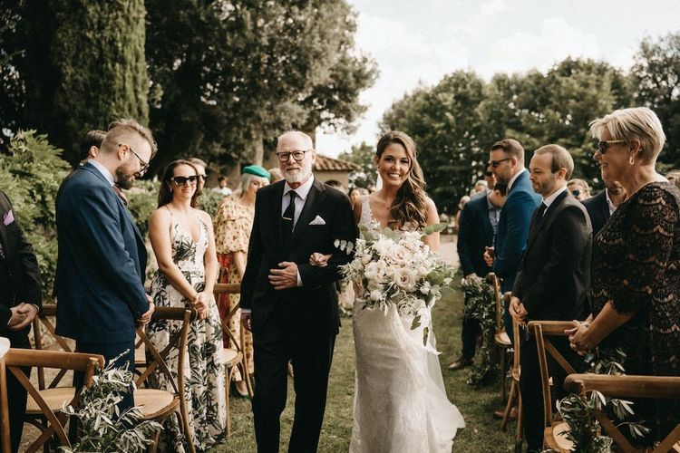 Bride walks down the aisle at Villa Le Fontanelle with blush bouquet