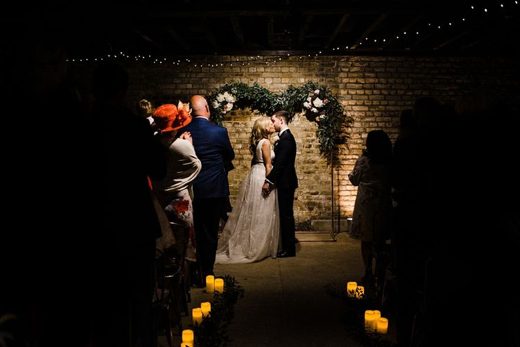Wedding Ceremony | Candle Aisle, String Lights & Floral Garland Wedding Decor | Bride in Ted Baker Wedding Dress | Groom in Tuxedo | The Electricians Shed, Trinity Buoy Wharf Wedding Planned by Utterly Wow | Claudia Rose Photography
