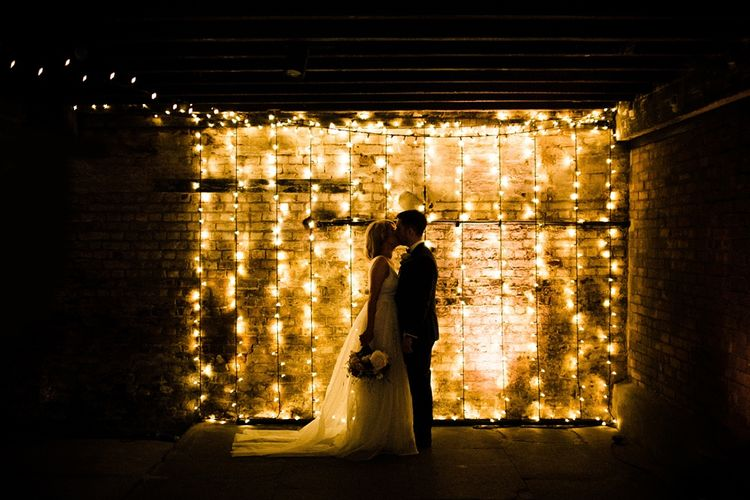 Fairy Lights Backdrop | Bride in Ted Baker Wedding Dress | Groom in Tuxedo | The Electricians Shed, Trinity Buoy Wharf Wedding Planned by Utterly Wow | Claudia Rose Photography
