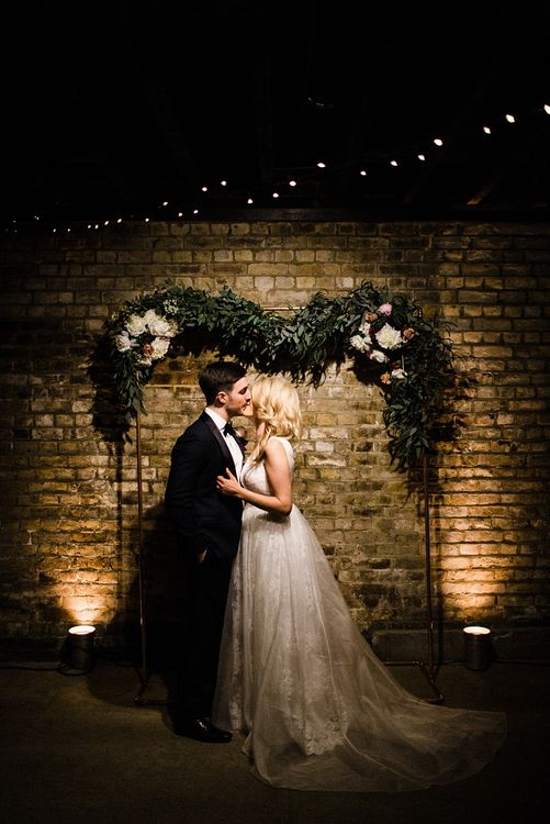 String Lights, Floral Garland Wedding Decor | Bride in Ted Baker Wedding Dress | Groom in Tuxedo | The Electricians Shed, Trinity Buoy Wharf Wedding Planned by Utterly Wow | Claudia Rose Photography