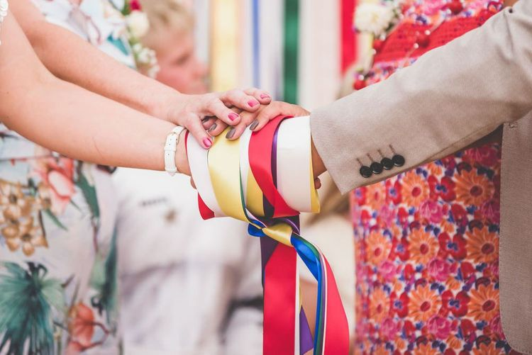 Brightly coloured ribbon hand fasting at marquee village fete themed celebration